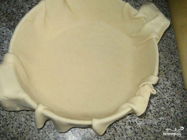 Дрожжевое тесто раскатать тонким пластом и застелить смазанную маслом форму для выпекания.