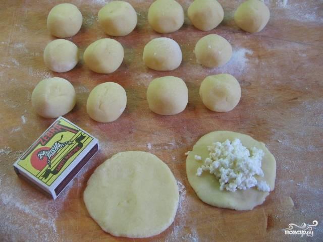4. Получившееся тесто раскатайте, не толсто, но и не очень тонко, чтобы кнели не развалились. Сформируйте кружки из теста, в середину выложите начинку из брынзы, затем залепите края, чтобы в результате получились шарики.