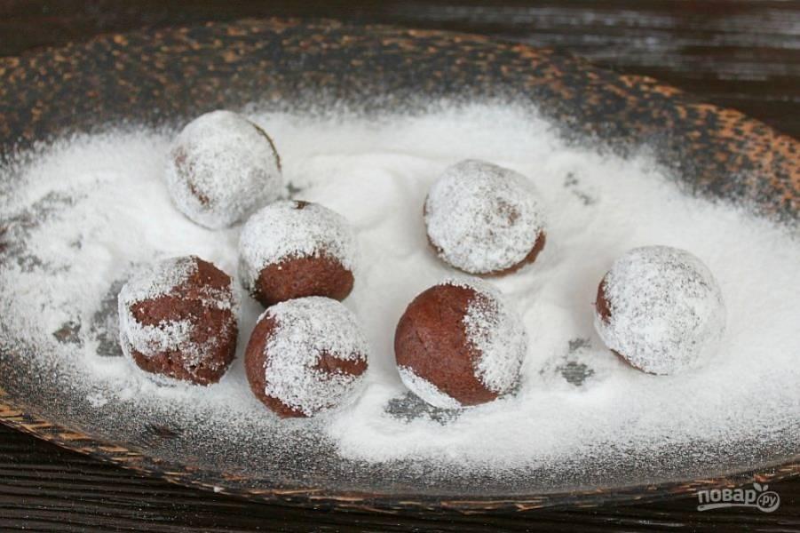 Через час шоколадное тесто застыло и можно сделать из него круглое печенье. Кружочки теста обваливаем в сахарной пудре и немного прижимаем.
