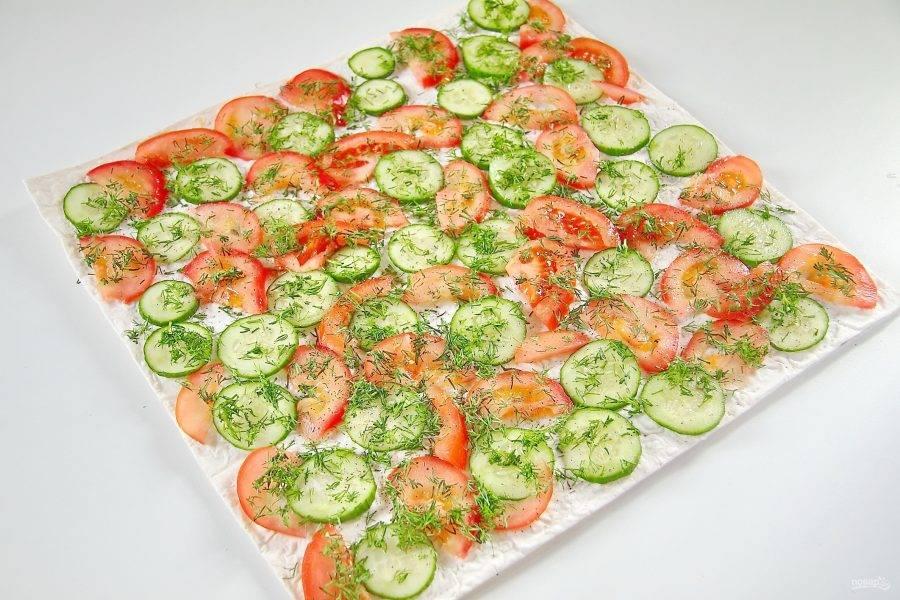 Сверху положите второй лаваш и разложите нарезанные овощи. Посыпьте их солью и зеленью. Можно добавить черный молотый перец по желанию.