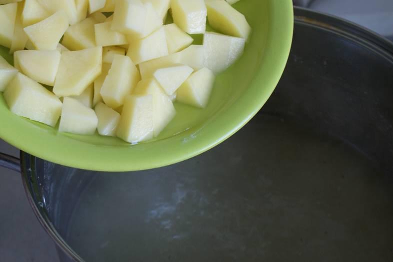 Окорочка сварились, извлекаем их из кастрюли. Цельную луковицу и морковь отправляем в мусорное ведро. Добавляем в бульон картофель, порезанный кубиками. Солим по вкусу, варим еще 10 минут.