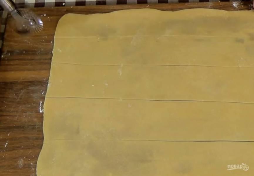 3. Накройте миску пленкой и поставьте в холодильник на 1 час. Разделите тесто на три одинаковые части. Одну из них раскатайте в прямоугольник, а остальные оставьте в холодильнике. Прямоугольник разрежьте на пять одинаковых полос.