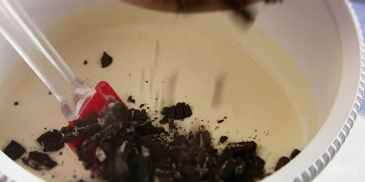 2. Печенье разрежьте ножом на небольшие кусочки, добавьте к мороженному и перемешайте. Переложите массу в стеклянную или пластиковую мисочку.