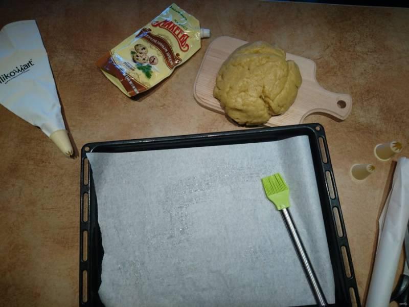 6. Тесто вымесите руками, посыпайте мукой при необходимости. Противень застелите пергаментной бумагой. Бабушка рекомендовала смазать бумагу маслом, но это необязательно.