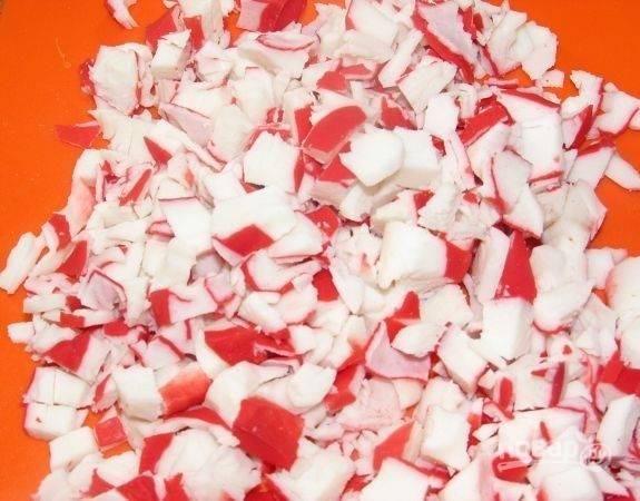 Нарежьте крабовые палочки, также добавьте их в салат. Посолите всё.