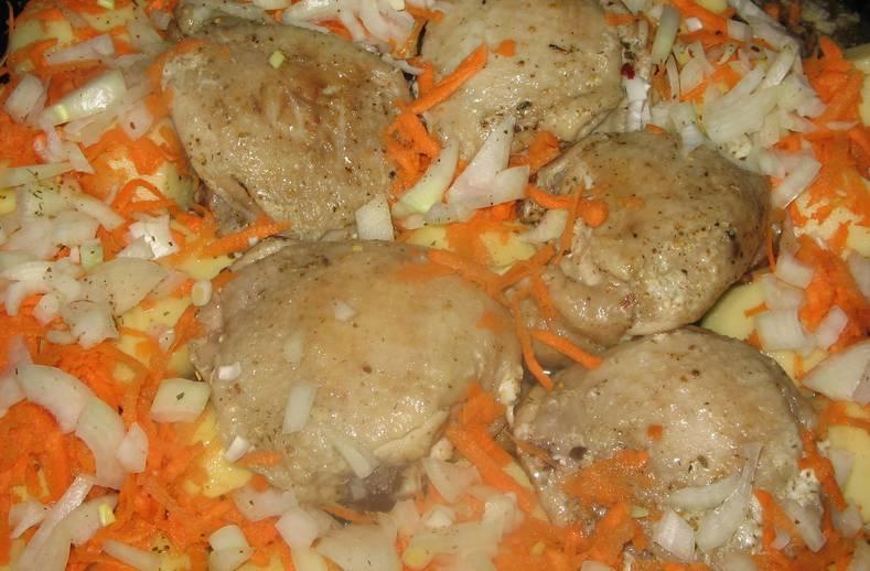 Посыпаем блюдо тертой морковью и измельченным луком. Готовим 30 минут, через 15 минут переворачиваем бедра и овощи на другую сторону.