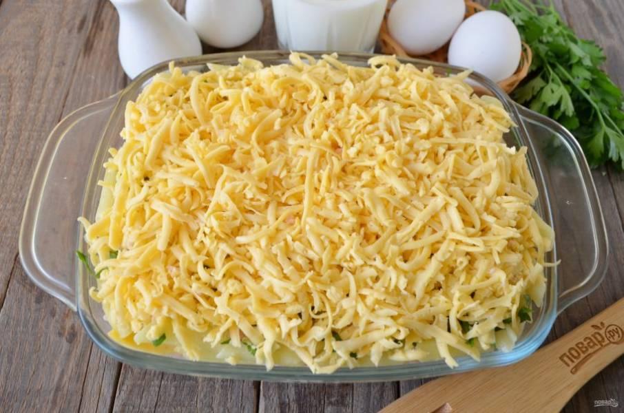 Сверху щедро засыпьте пирог тертым сыром, утрамбуйте немного руками.