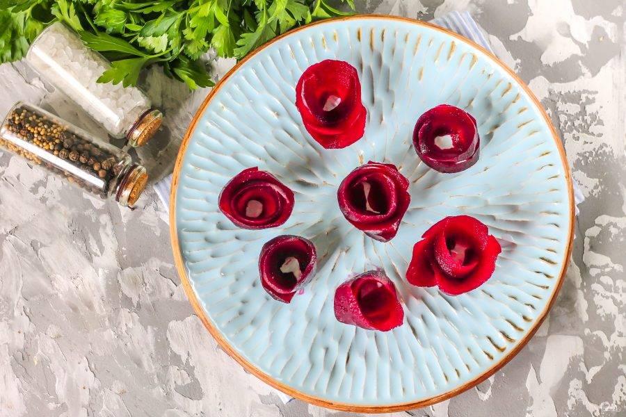 Очистите отварную свеклу от кожуры, промойте и нарежьте лентами, точно так же, как будто вы срезаете кожуру с яблок. Свекольные ленты промокните бумажным полотенцем, чтобы они не выделяли сок. Скрутите из них розы и выложите на тарелку.
