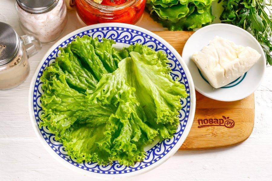 Промойте листья салата в воде, обсушите бумажными салфетками и выложите на тарелку.