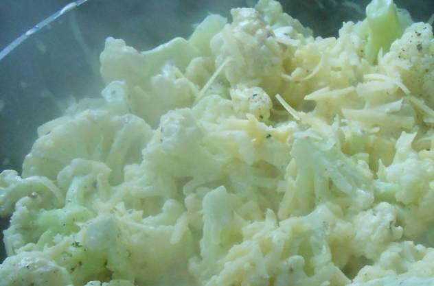 2. Дно формы для запекания смажем маслом. Выкладываем капусту, заливаем соусом. Оставшийся сыр натираем крупно и посыпаем блюдо сверху. Запекаем 20 минут при 200 градусах.