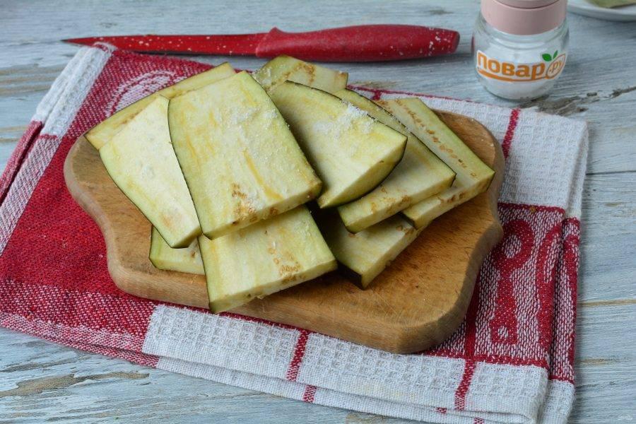 Баклажаны нарежьте средними пластинами и присыпьте солью по вкусу. Оставьте на 10-15 минут, чтобы вышла горечь.