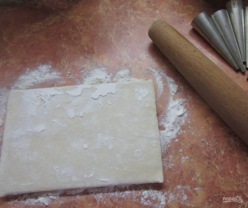 1. Когда под рукой есть готовое слоеное тесто, то приготовить такие пирожные еще проще и быстрее. Для начала тесто нужно немного разморозить, после чего каждый пласт следует раскатать толщиной не более 0,5 см.