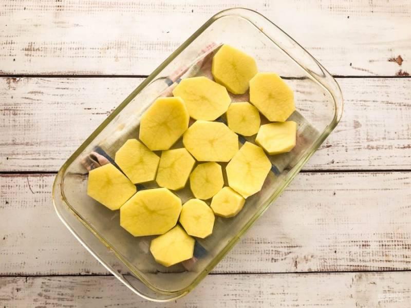 Картофель хорошо помойте, очистите и нарежьте кружочками. Возьмите жаропрочную форму, смажьте ее растительным маслом и выложите нарезанный картофель.