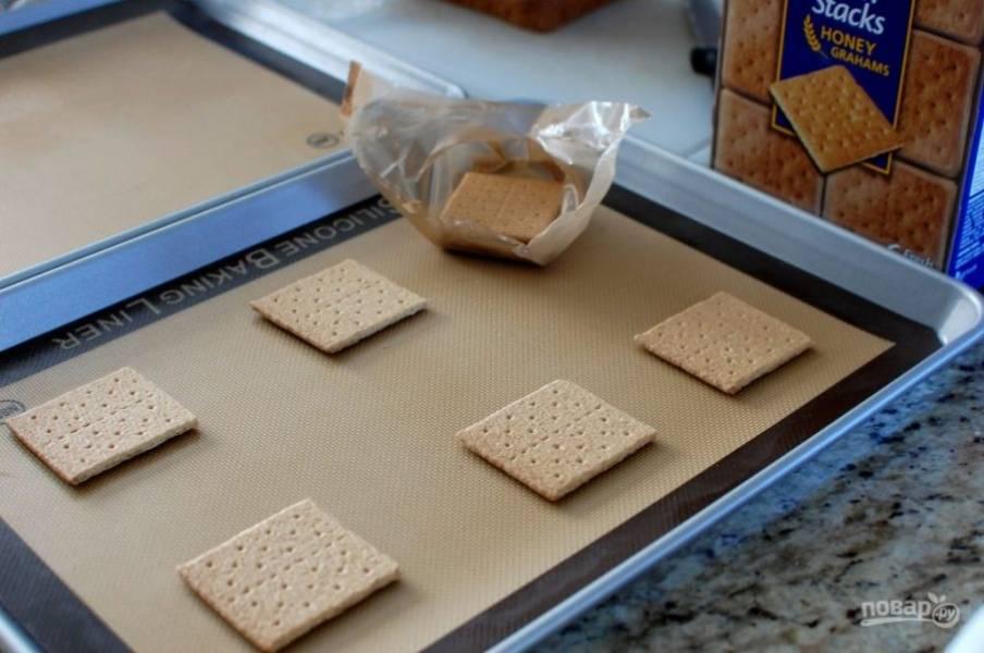 5.На противень, застеленный пергаментом или силиконовым ковриком, выложите крекеры.