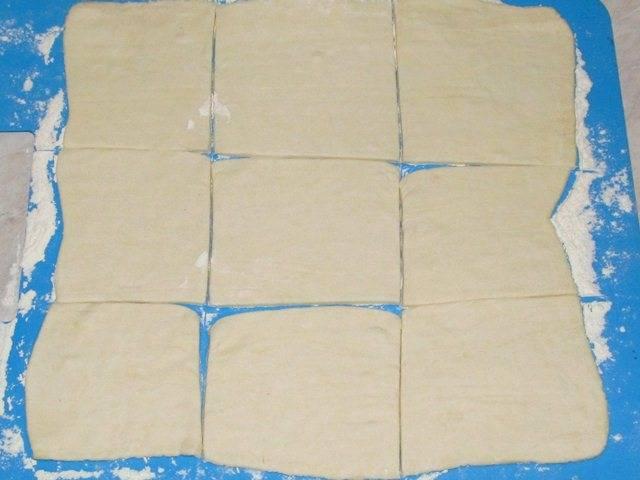 Готовое слоеное тесто слегка раскатываем и нарезаем на квадраты. Стороны квадратов - от 8 до 10 см. Из квадратиков такого размера получатся небольшие и аккуратные слойки.