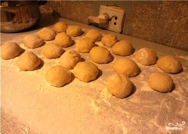 Смешать муку, сухие дрожжи, половину чайной ложки соли, добавить масло и теплую воду. Замешать тесто, сформировать шар, оставить в теплом месте под полотенцем на 1 час. Затем еще раз обмять тесто - и еще на полчаса под полотенцем. Подошедшее тесто скатываем в колбаску, которую разрезаем на кусочки равного размера.