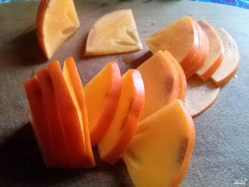 Хурму и яблоки порежьте тонкими дольками. Капусту порвите на небольшие кусочки. Грудку порежьте на маленькие кусочки.