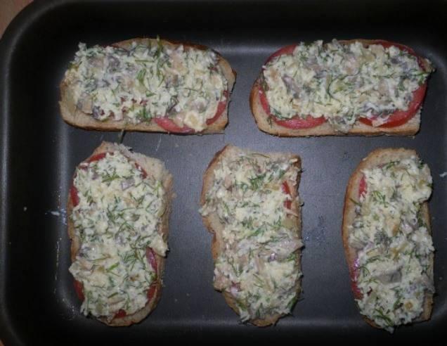 Полученную смесь распределите на бутербродах, поверх помидоров и отправьте в духовку запекаться при 180 градусах на 10 минут. Подайте на стол в горячем виде.