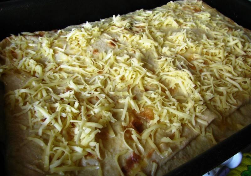 Сверху положите лист лаваша, повторите слой начинки. Повторяйте слои лаваша и начинки, пока что-то из них не закончится. Сверху смажьте яйцом и отправьте в разогретую до 200 градусов духовку на 25 минут.