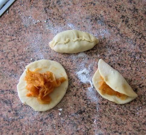 5. Теперь из подготовленного теста формируем лепешечки, и в каждую помещаем начинку. Выкладываем на форму, смазанную маслом и застланную пергаментной бумагой.