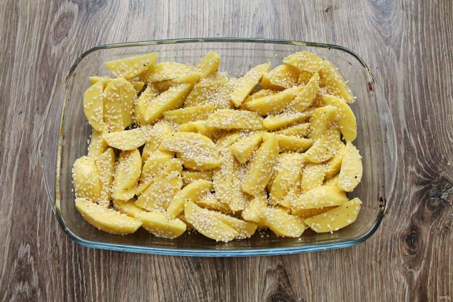 Переложите картофель в форму для запекания в один слой и хорошенько посыпьте верх кунжутом.