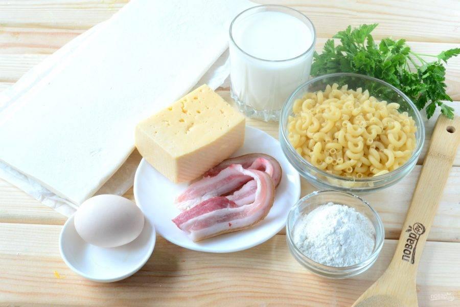 Подготовьте все необходимые ингредиенты. Слоеное тесто уже должно лежать на столе минут 15. Сразу же ставьте на огонь кастрюльку с водой, чтобы варить макароны, и включайте духовку.