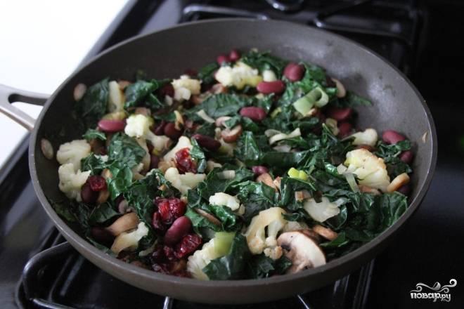 5. Сушеную клюкву залейте кипятком на несколько минут, затем слейте. Добавьте в сковороду нарезанный листовой салат, фасоль и клюкву. Посолите, поперчите и залейте овощи готовым бульоном. Тушьте их еще в течение 5 минут.