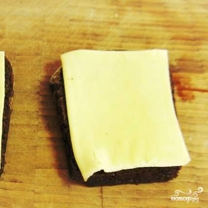Черный хлеб нарезаем ломтями, на каждый из них кладем ломтик сыра.