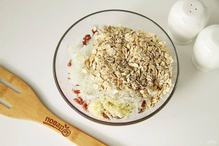 Добавьте тертый на крупной терке лук, измельченный чеснок, овсяные хлопья (по желанию), соль и перец по вкусу.