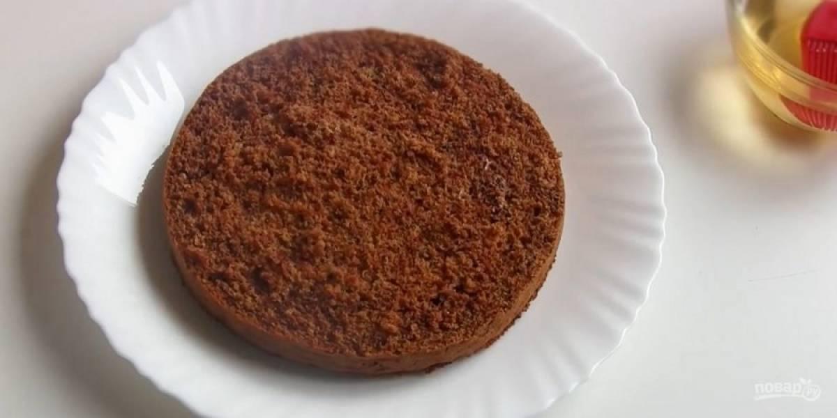 4. Какао смешайте с растительным маслом и добавьте к крему. Снова перемешайте крем миксером. Бисквит разрежьте на три части. Приготовьте сироп: воду с сахаром подогрейте до растворения сахара, слегка остудите и добавьте коньяк.