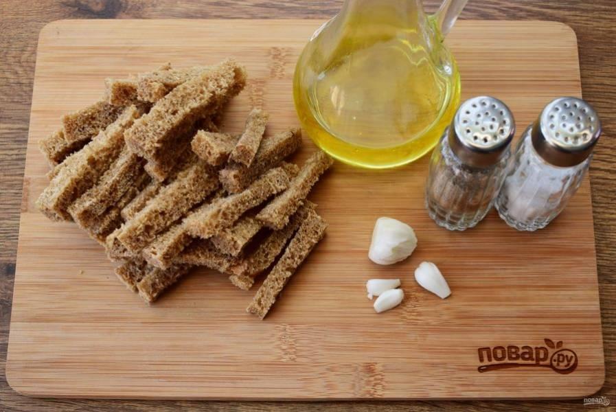 Хлеб нарежьте на ломтики, обрежьте у него корочки. Нарежьте брусочками. Чеснок очистите.