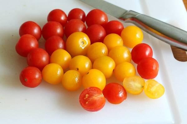 2. Помидоры вымыть и обсушить. Чтобы салат с черри и сыром в домашних условиях был более красочный, помидоры можно взять красные и желтые. Нарезать их пополам.