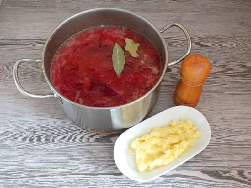 Достаньте рульку. Добавьте в кастрюлю обжаренные свёклу с луком, мятый картофель с чесноком, лавровый лист, перец и соль по вкусу. Поставьте на медленный огонь. Нагревайте, но не кипятите.