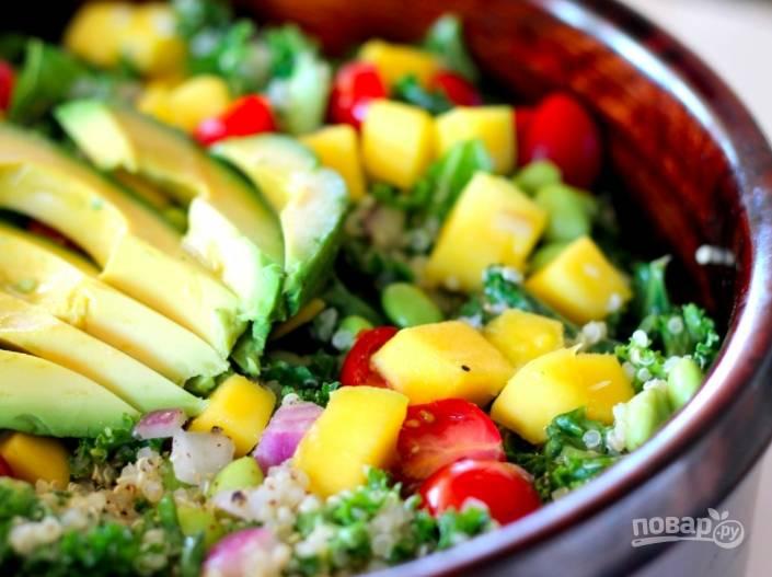 В салатницу выложите кале, порванную руками на кусочки. Помидоры, лук и манго смешайте с киноа и заправкой, выложите на капусту. Авокадо очистите и нарежьте дольками, выложите на салат.