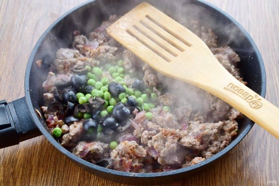Добавьте измельченные маслины и зеленый горошек, перемешайте.