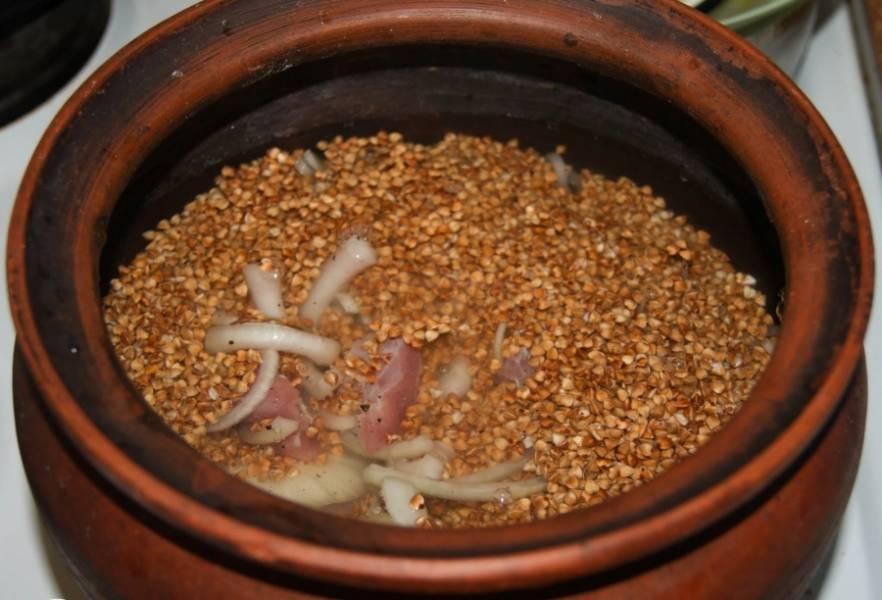 Переложите мясо и лук в горшочек, сверху засыпьте промытой крупой. Посолите и залейте бульоном или водой. Накройте горшочек крышкой.