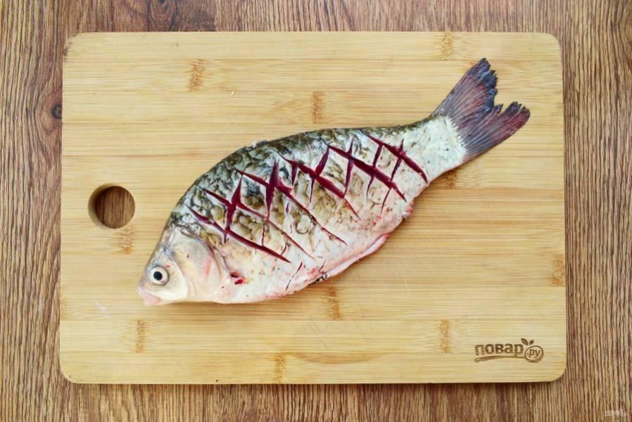 Рыбу выпотрошите, почистите, удалите плавники, промойте под холодной водой. Сделайте частые надрезы по диагонали, крест на крест, по тушке рыбы с обеих сторон.