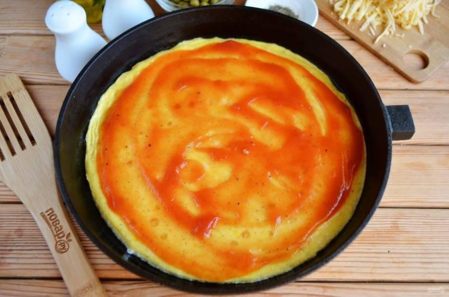 Готовый омлет чуть остудите и смажьте томатным соусом.