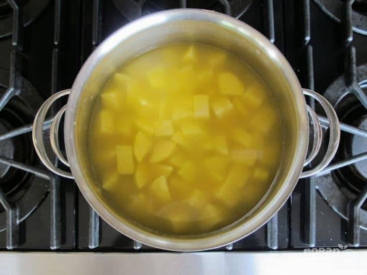 1. Картофель почистите и нарежьте на кубики. Поставьте его в бульоне на огонь. Доведите до кипения, а потом варите 25 минут до мягкости.
