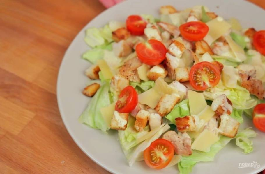 4. Поджарьте куриную грудку с обеих сторон до золотистого цвета, посолив и поперчив ее. Затем соберите салат: выложите на листья салата сухарики, нарезанную куриную грудку, нарезанный тонкими пластинками пармезан и помидоры черри. Заправьте салат соусом. Приятного аппетита!