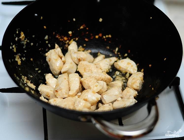 Куриное филе нужно промыть и обсушить немного. Нарезаем его острым ножом небольшими, довольно узкими дольками. Размер кусочков должен быть таким, чтобы впоследствии их можно было удобно брать палочками. Обжариваем курицу в воке с чесноком и имбирем. По желанию курицу можно посолить, хотя я предпочитаю использовать только соевый соус.
