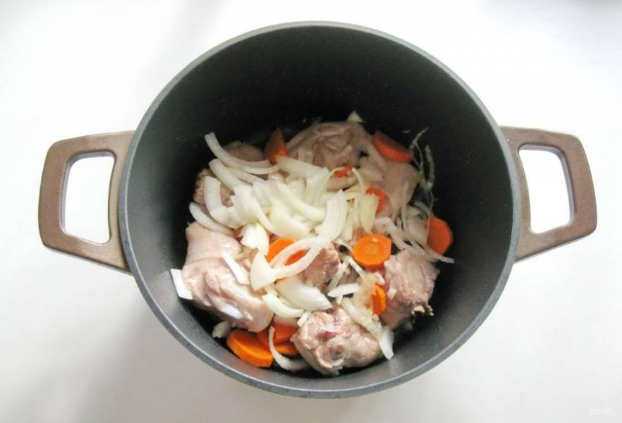 Морковь и репчатый лук очистите, помойте и нарежьте произвольно. Добавьте в кастрюлю к курице.