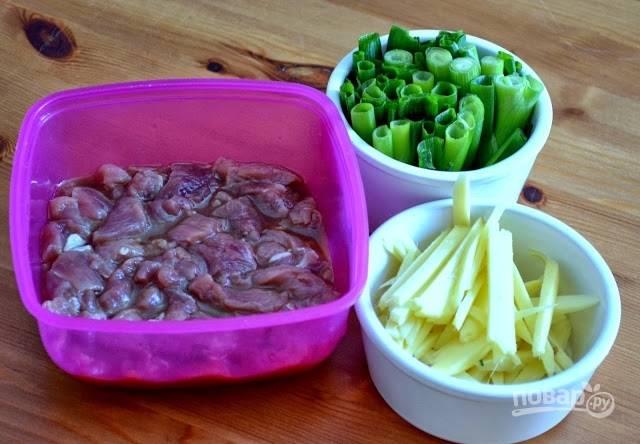 1. Нарежьте свинину тонкими полосочками. Выложите в небольшую мисочку, добавьте соевый соус, уксус, рисовое вино, щепотку перца, сахар. Оставьте мариноваться.  Параллельно очистите и измельчите имбирь, крупно нарежьте зеленый лук.