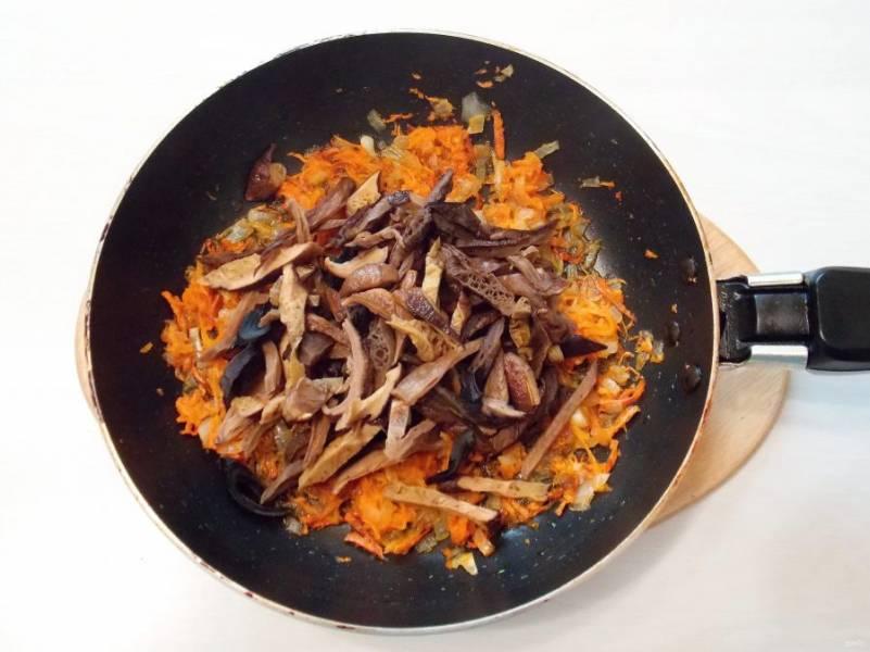 Замоченные грибы порежьте соломкой и добавьте в сковороду с овощами. Обжаривайте овощи с грибами на среднем огне в течение 7 минут.