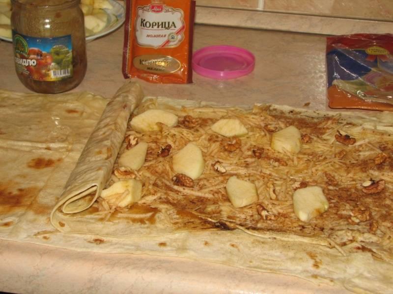 2. Лаваш расстилаем, смазываем медом, выкладываем на него яблоки и орехи. Посыпаем ванилью и корицей (по желанию), и сворачиваем рулетом.