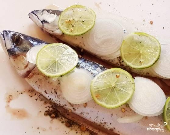 Лук очистите и нарежьте кольцами. Лайм вымойте и также нарежьте колечками. Обложите рыбу со всех сторон лаймом (который можно заменить на лимон) и луком. Полейте немного оливковым маслом.