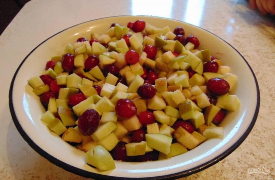 Пока сделайте начинку. Клюкву смешайте с яблоками, нарезанными мелкими кубиками. Добавьте сахар и крахмал. Перемешайте.