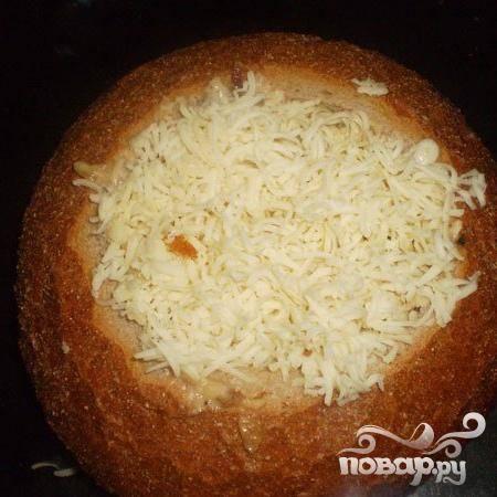 5.Срезаем с булки хлеба верхушку и мякоть удаляем. В булку выкладываем начинку. Натираем на терке сыр и посыпаем сверху начинки.