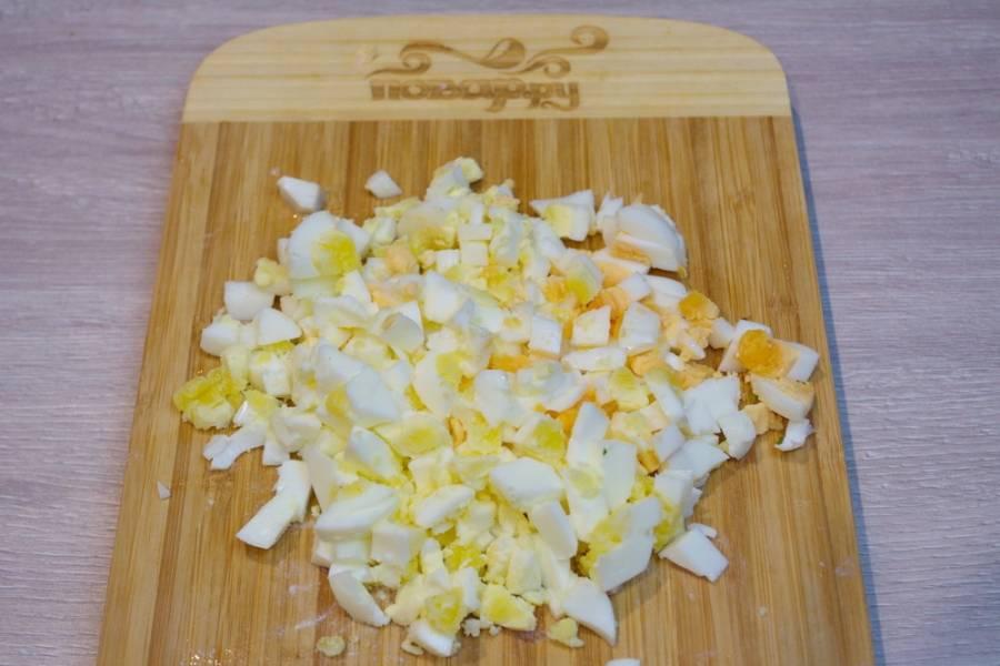 Отваренные куриные яйца нарезаем небольшими кубиками. Добавляем их также в салатник.