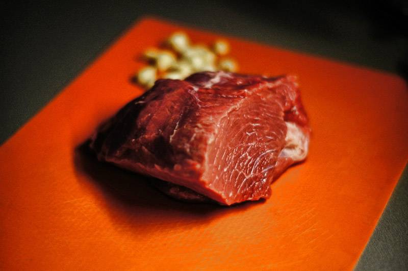 Для начала мы промываем мясо под проточной водой и вытираем его насухо бумажными полотенцами. Чеснок чистим и нарезаем пластинками, бараний жир режем на небольшие кусочки.